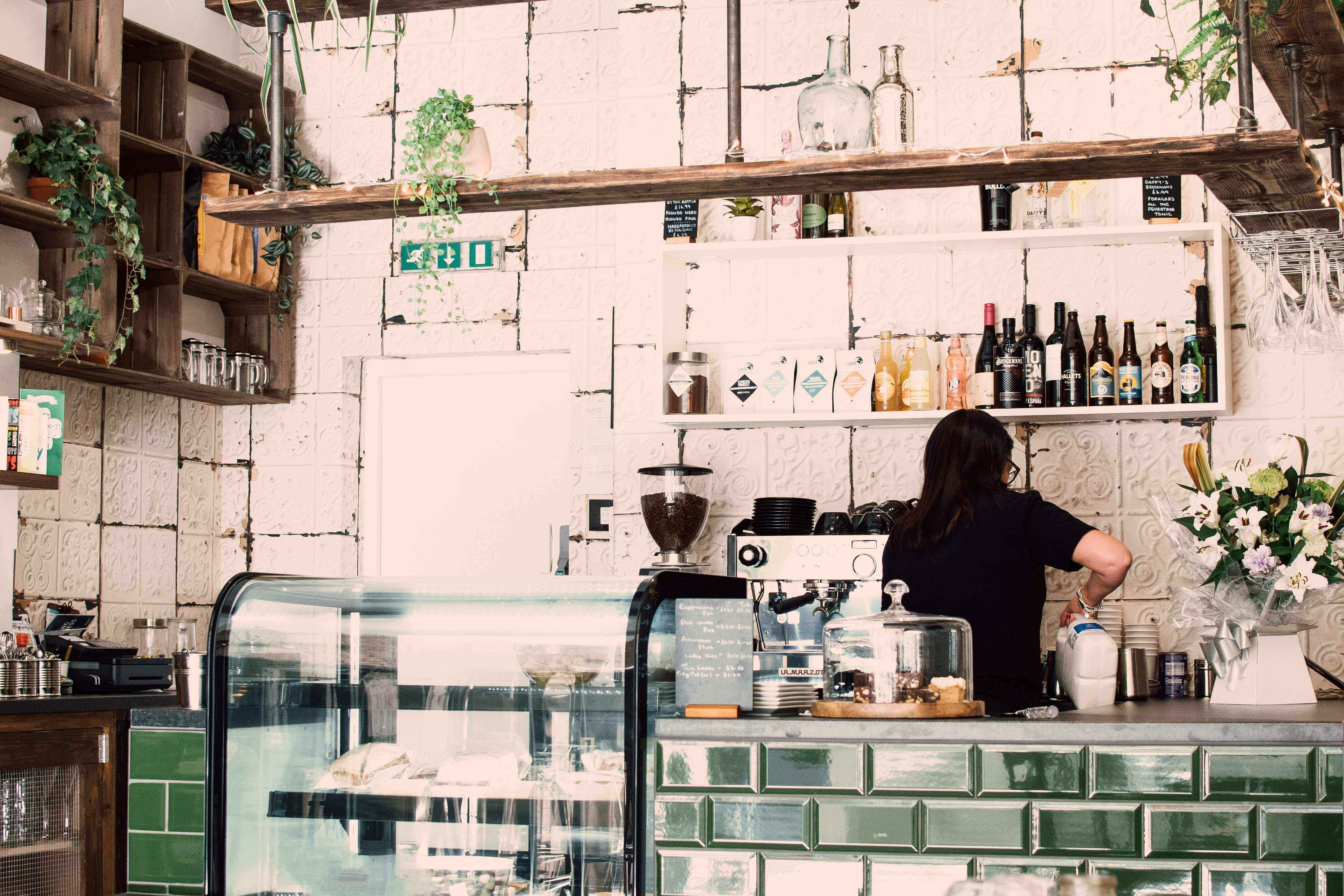 A barista behind the bar at a cafe making coffee