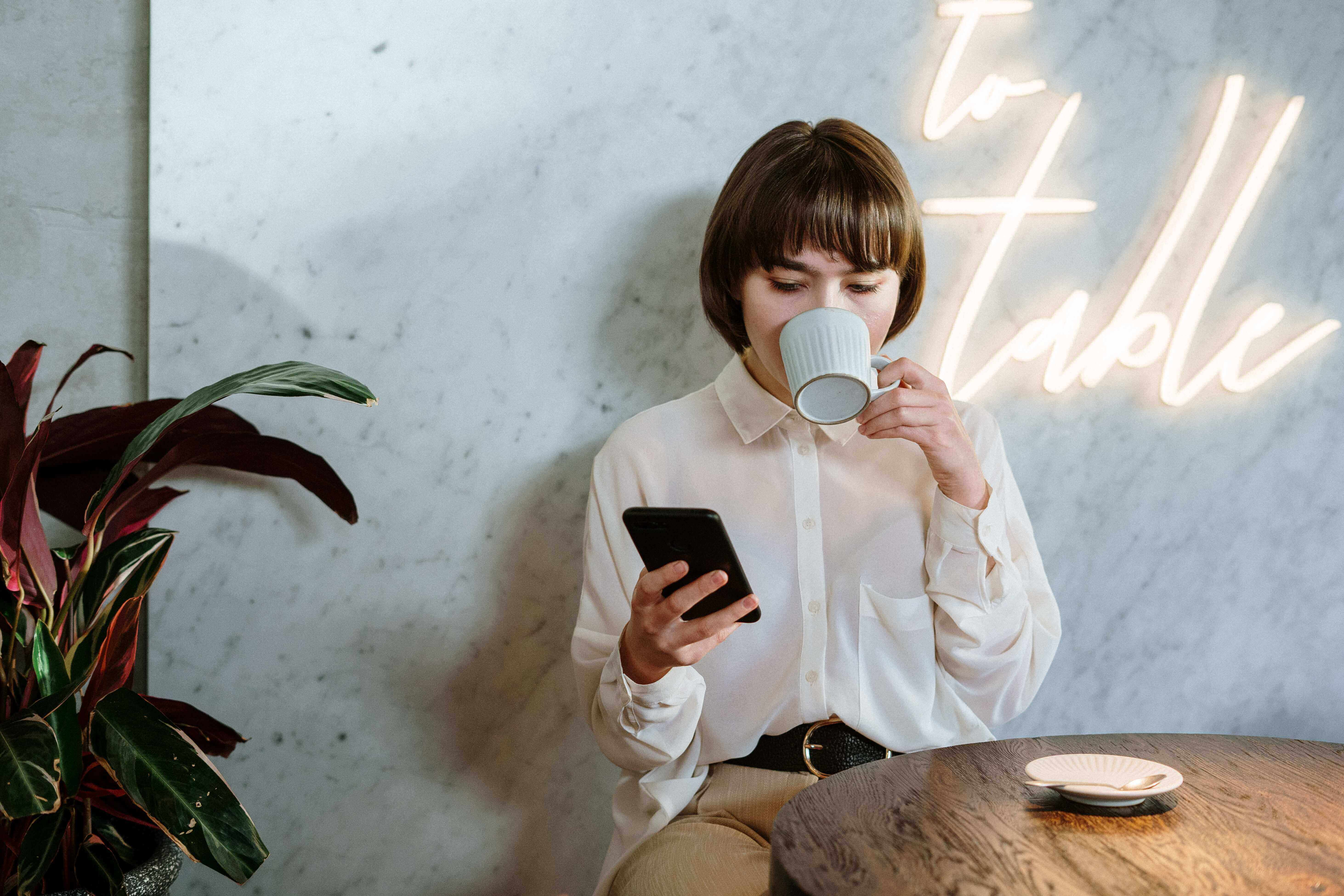 a woman drinking a coffee while looking at an app on her phone