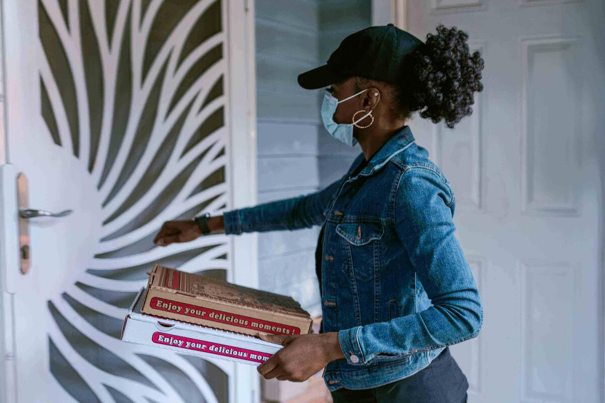 A woman delivering pizza to a door